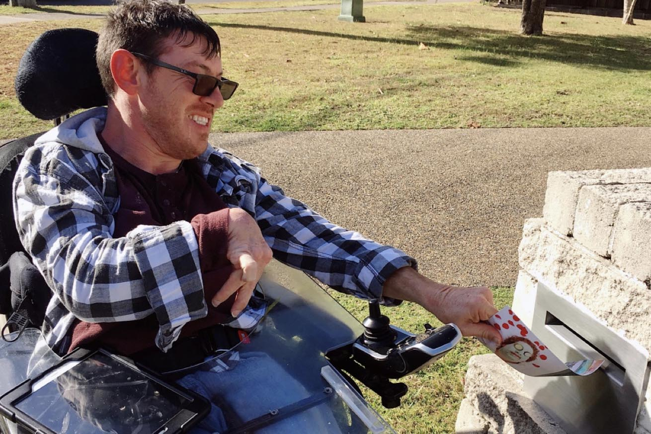 avenue participant in wheelchair putting flyer into letterbox